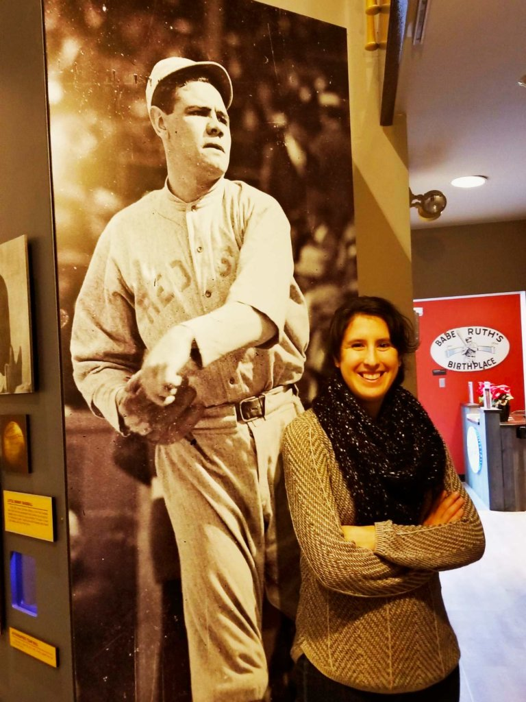A young woman leaning against a larger than life photo of Babe Ruth