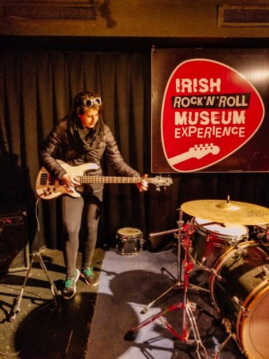 Young woman with a black coat playing bass at the Irish Rock and Roll Museum Experience