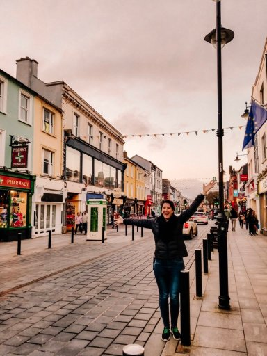 Young woman standing on the sidewalk in downtown Killarney Ireland looking excited with arms raised
