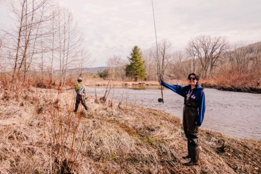 A triumphant young woman holding a fishing pole in the air in Berkshire County, MA with Berkshire Rivers Fly Fishing