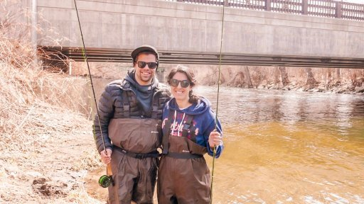 A young man and woman holding fishing poles and smiling near the river in Berkshire County, MA with Berkshire Rivers Fly Fishing