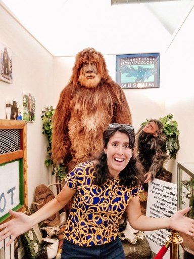 Young woman standing in front of a Sasquatch statue in Portland Maine