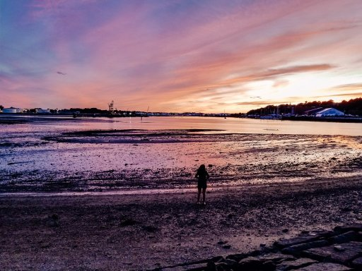 Young woman standing at the water's edge in South Portland, Maine with a beautiful sunset in the background
