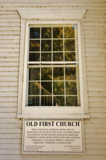 A window with a sign that says the old first church in bennington, vermont