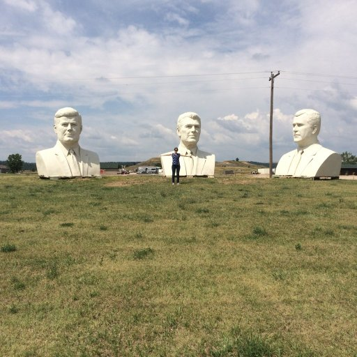 Young woman standing with a president head of Kennedy, Reagan, and Bush in South Dakota