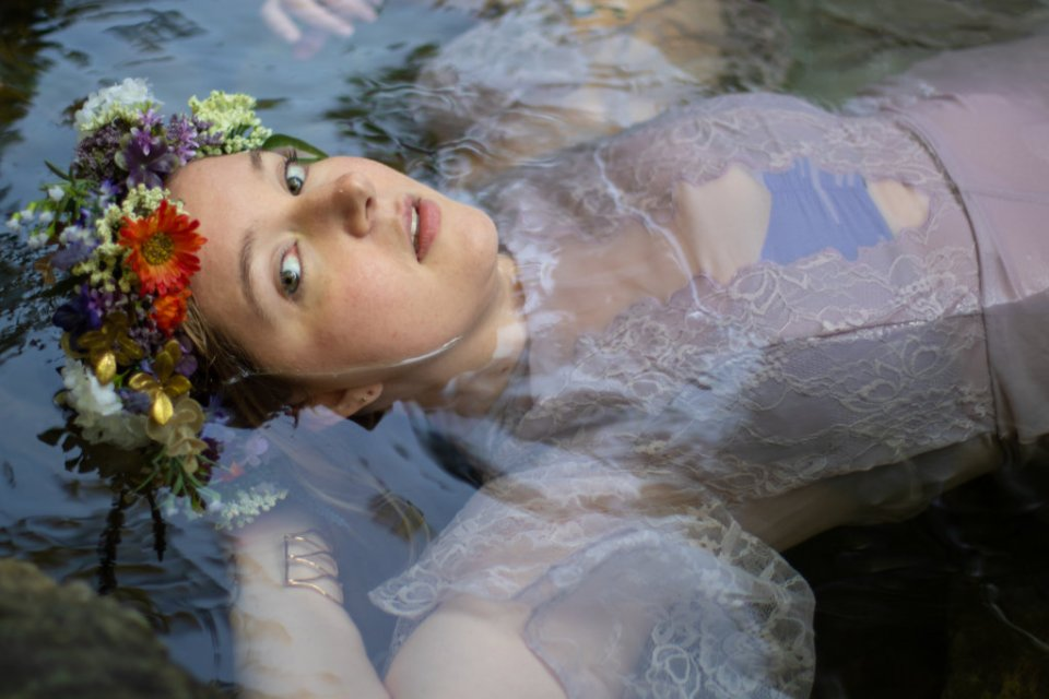 Girl in a purple dress with a flower crown in the water at Kilgore Falls photo shoot