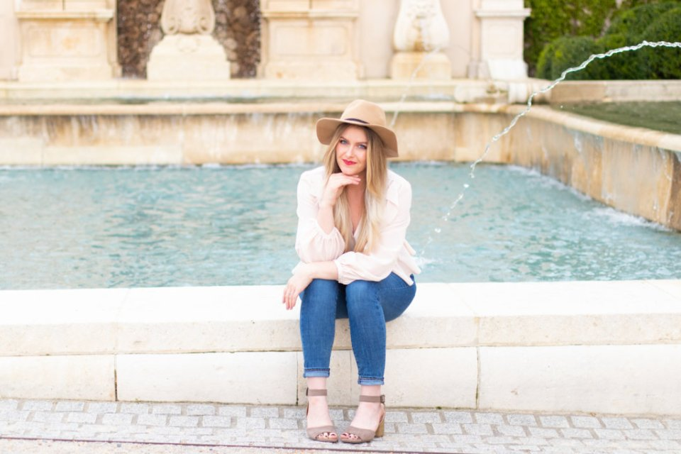 Renee, a white woman with blonde hair, sits on a ledge by a fountain with sandals, jeans, and a pink ruffled shirt on along with red lipstick and a hat.