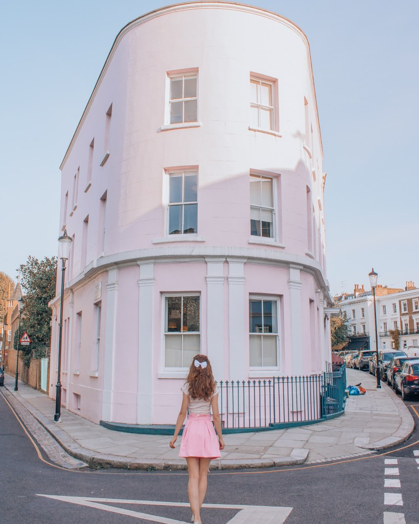 Girl in front of big pink house