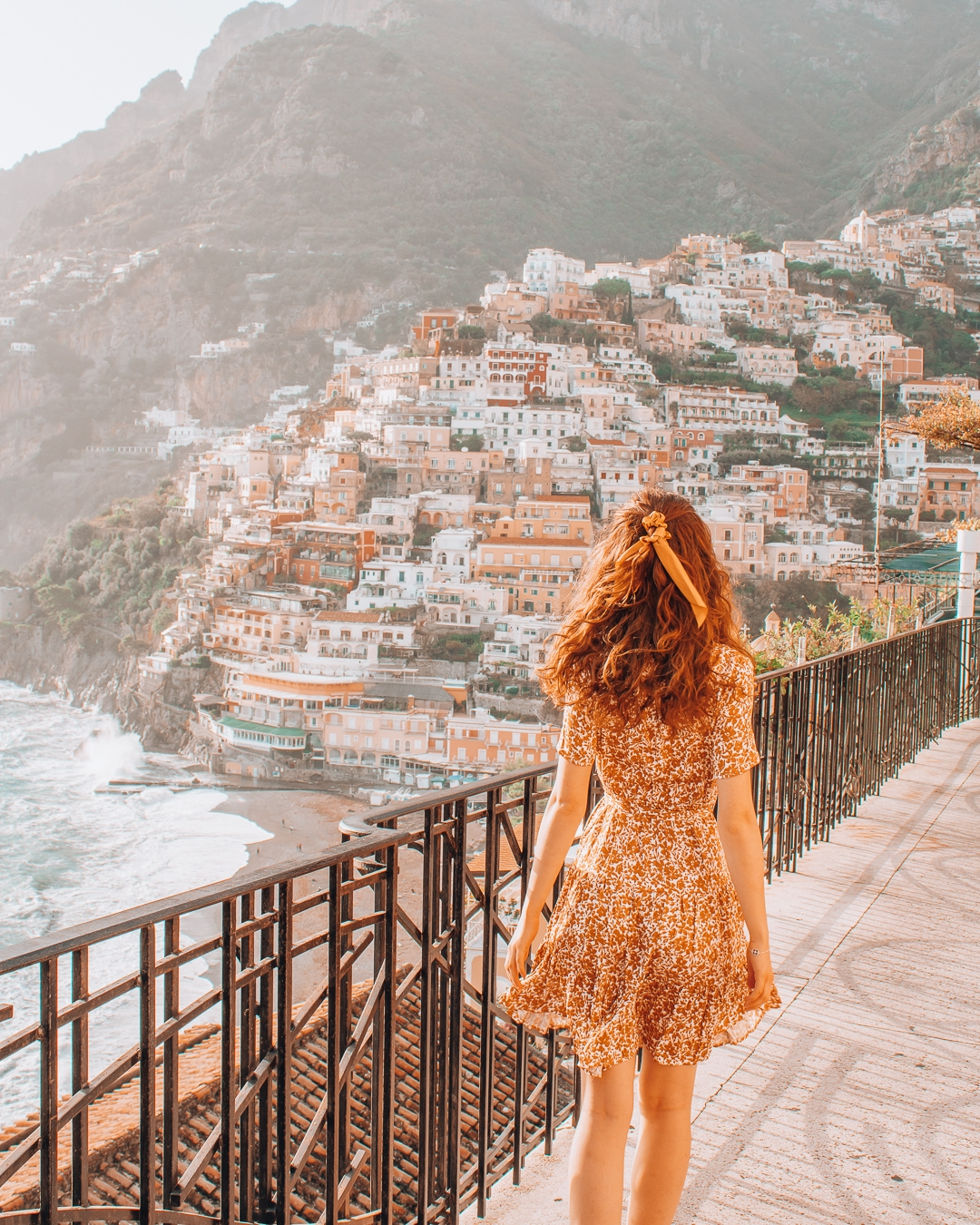 Girl on the sidewalk next to the road in Positano