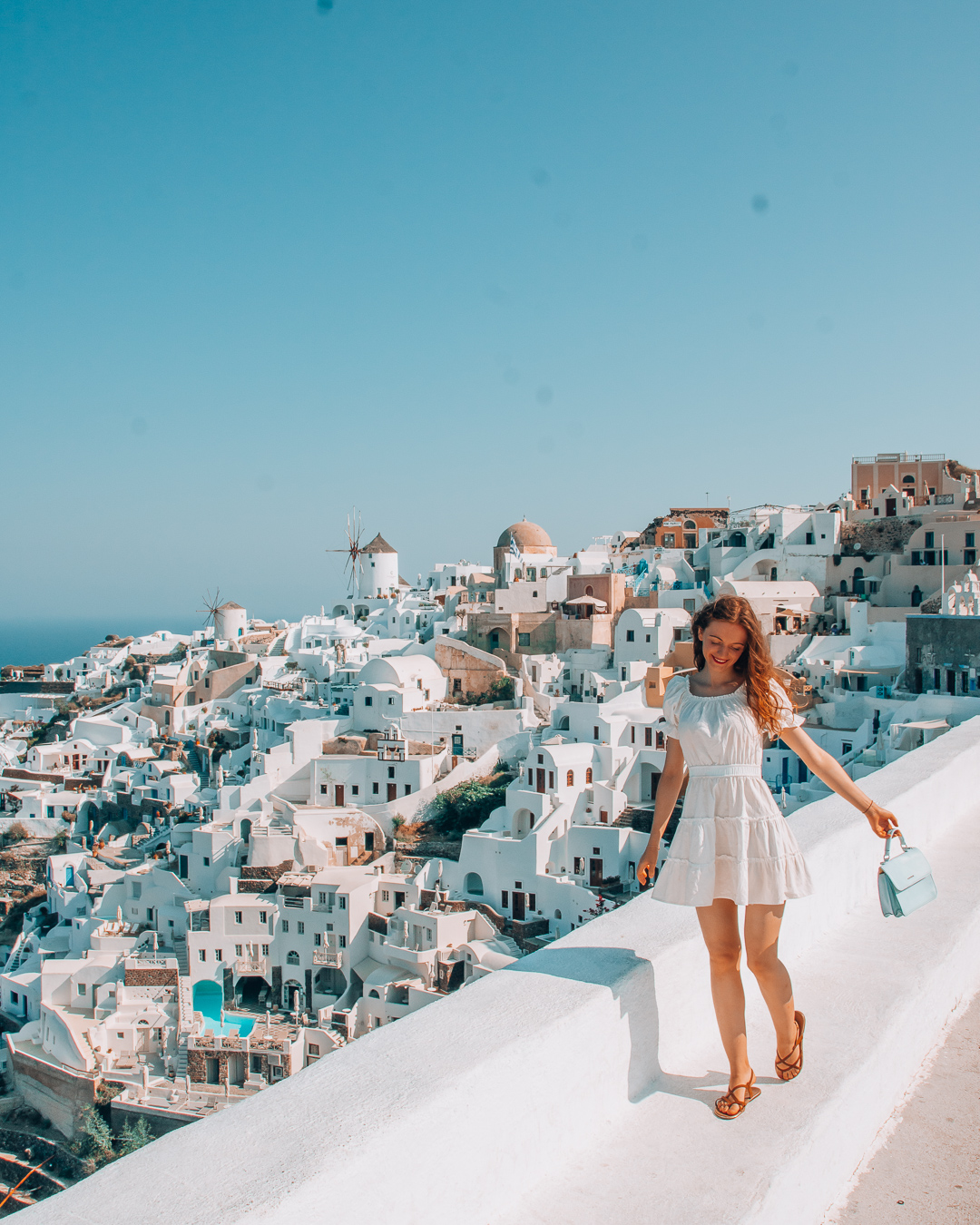 Happy girl at Oia Castle and view over white houses in Santorini