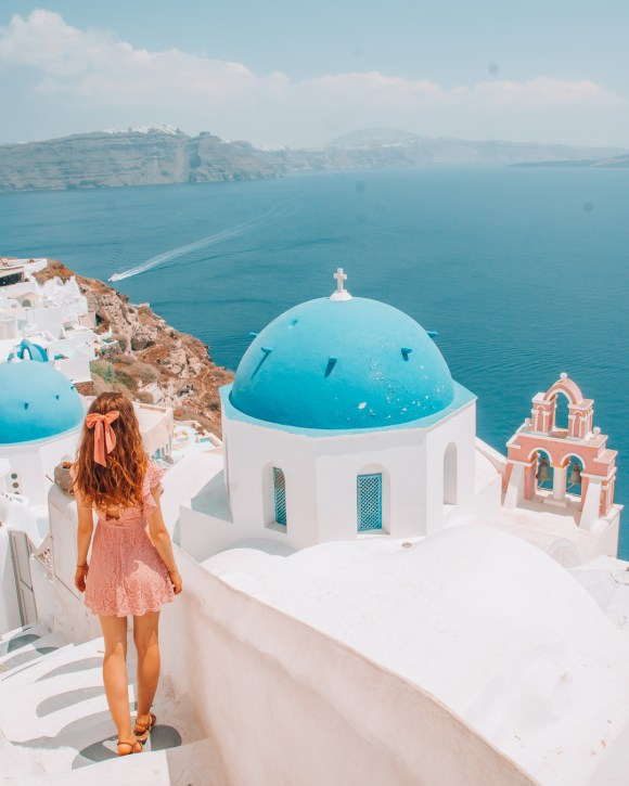 Girl walking on a path in Santorini overlooking Anastasia Church