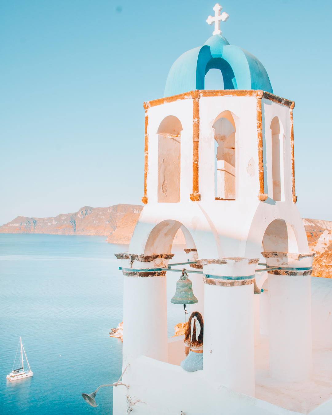 Girl sitting in a bell tower in Santorini