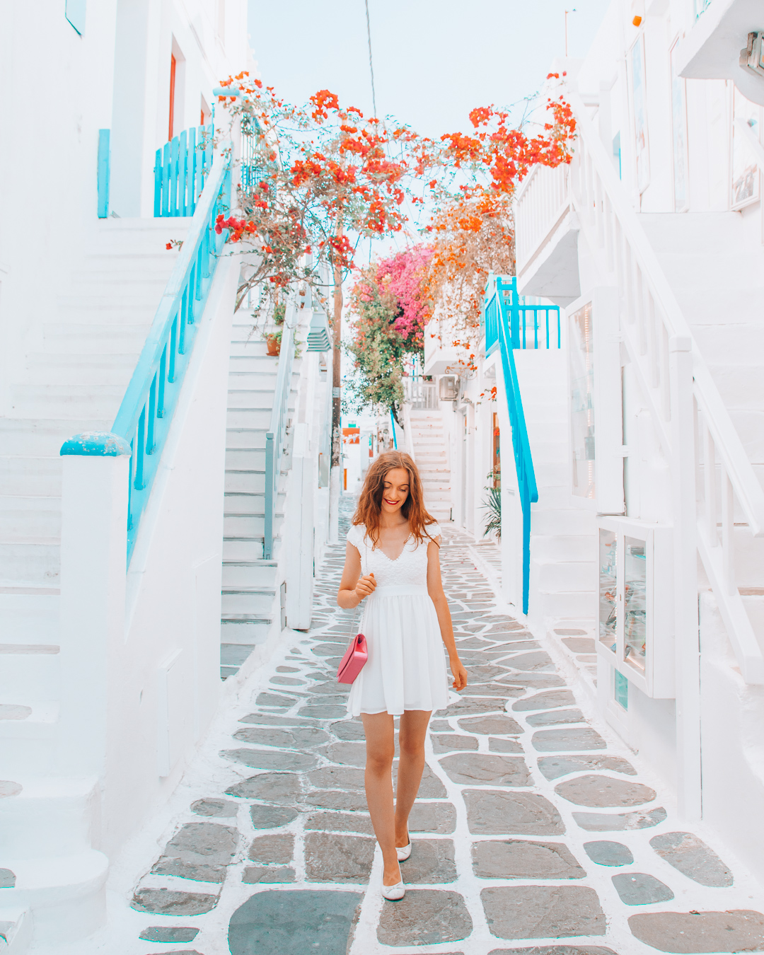Happy girl in street in Mykonos with cobblestones and flowers