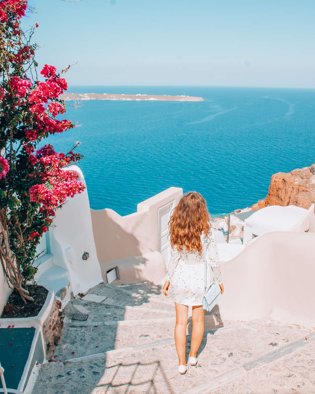Girl looking at a beautiful view in Santorini with the sea and pink flowers