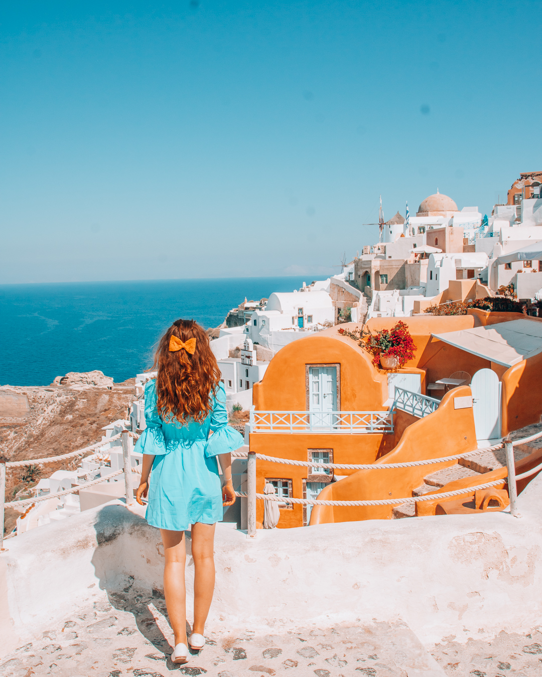 Girl with blue dress and orange bow lookng at Kastro Oia Houses