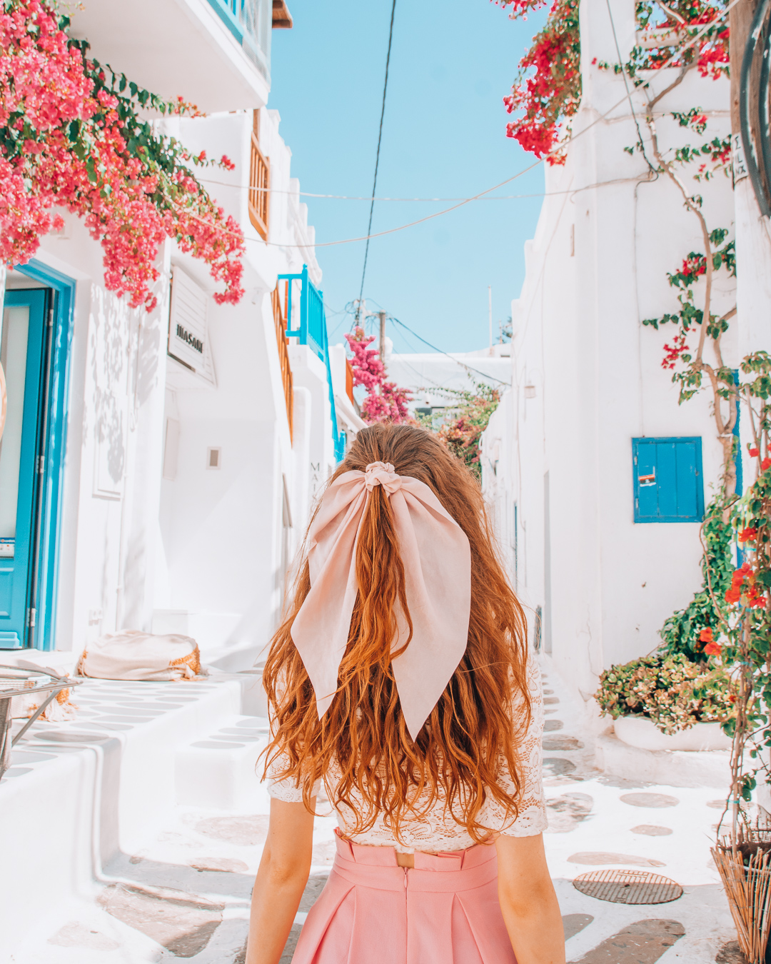 Girl looking at colourful street with flowers in Mykonos
