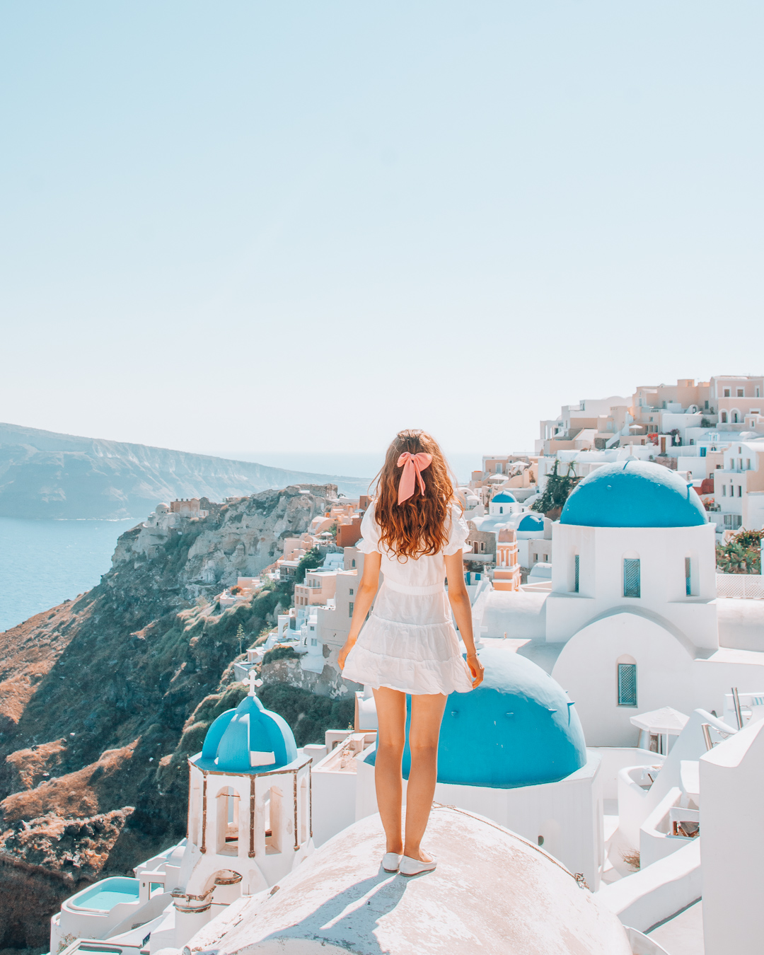 Girl standing on a rooftop in Santorini with blue domes in the background