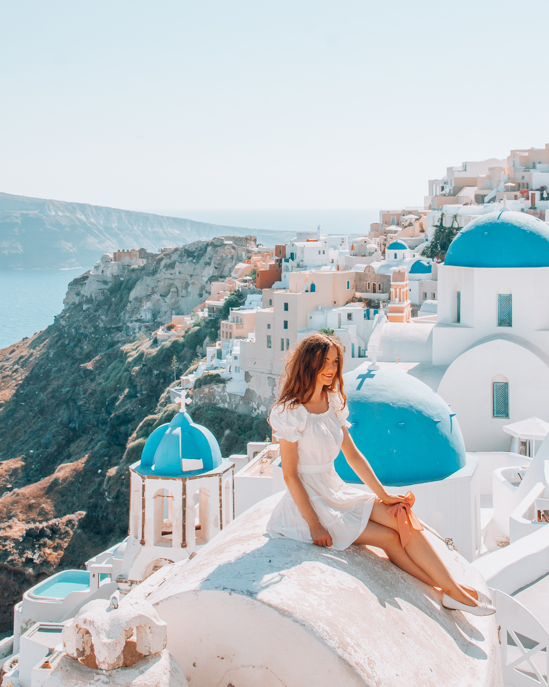 Girl sitting on a rooftop in Santorini with blue domes in the background