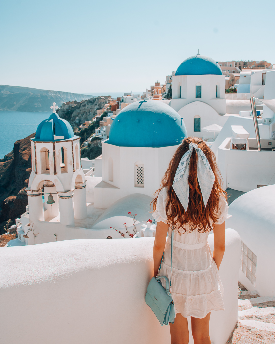 Girl walking towards the blue domes in Santorini
