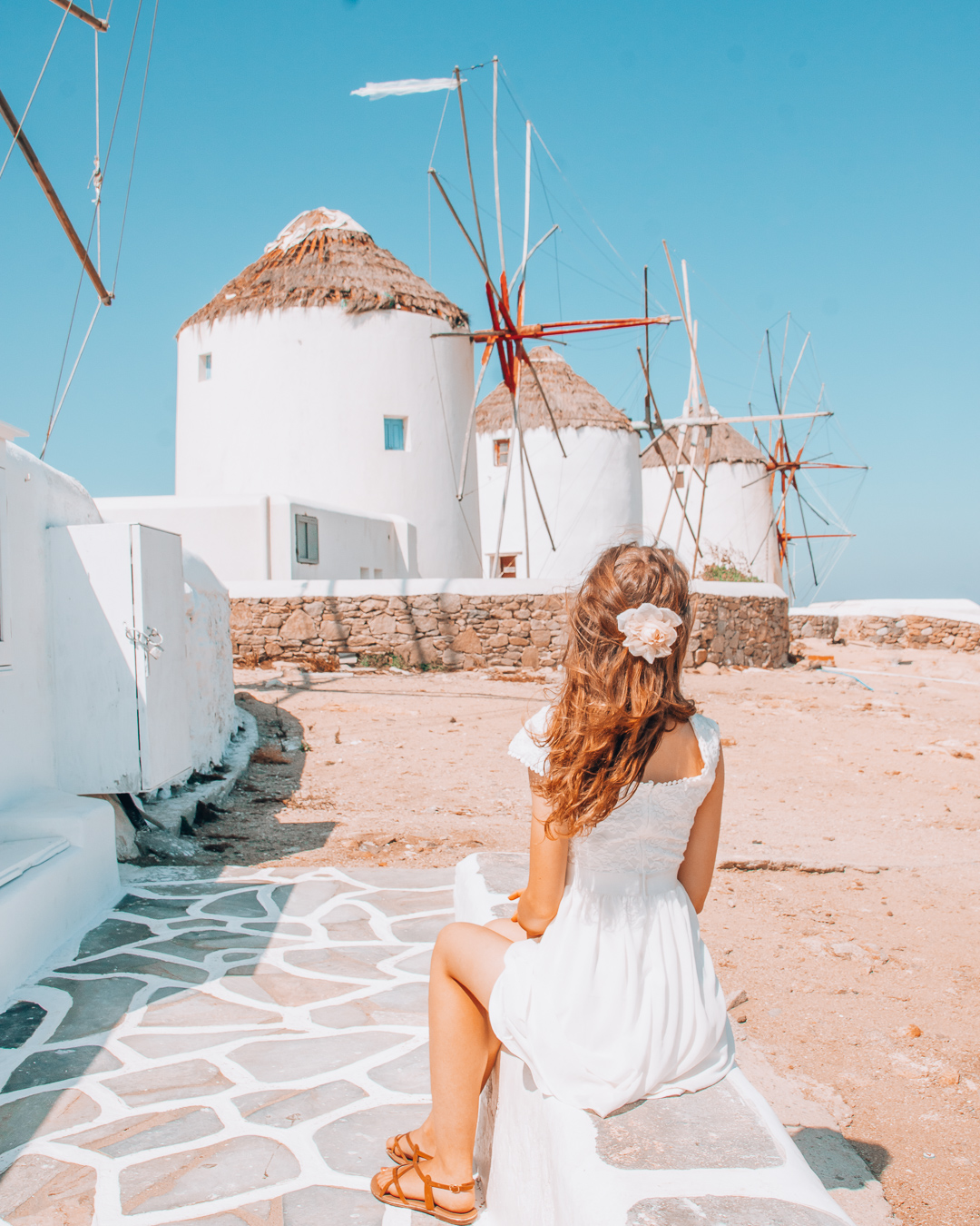 Windmills in Mykonos and a girl looking at them
