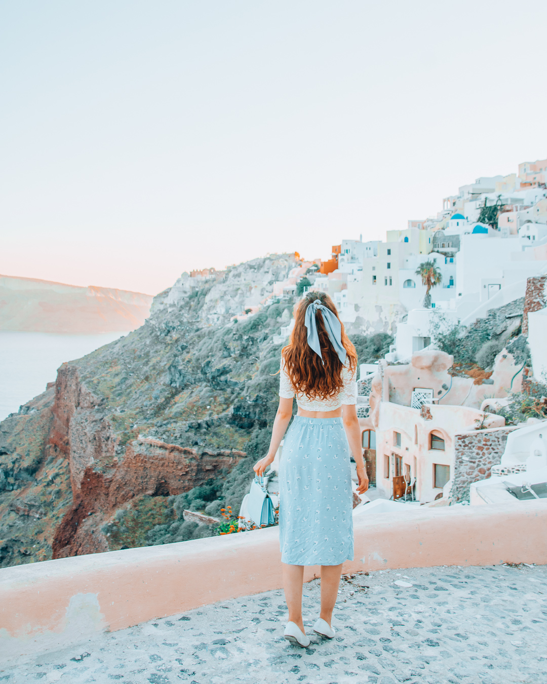 Girl enjoying a view over Oia from beneath