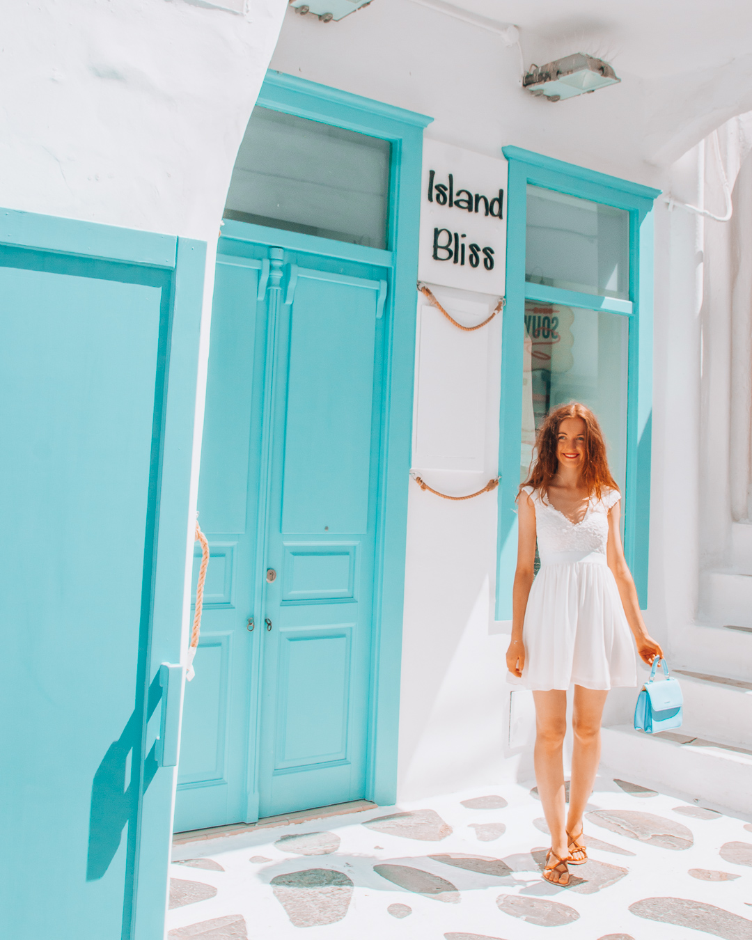 Girl with a white dress and a blue bag in front of a blue building in Mykonos