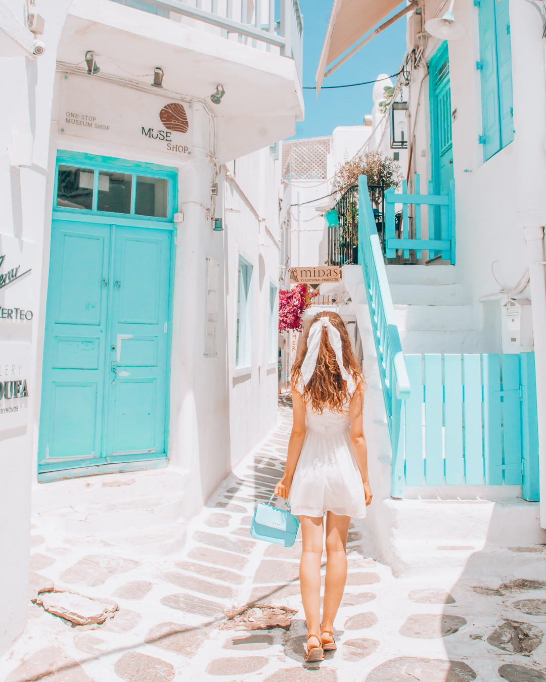 Girl walking in a blue street in Mykonos