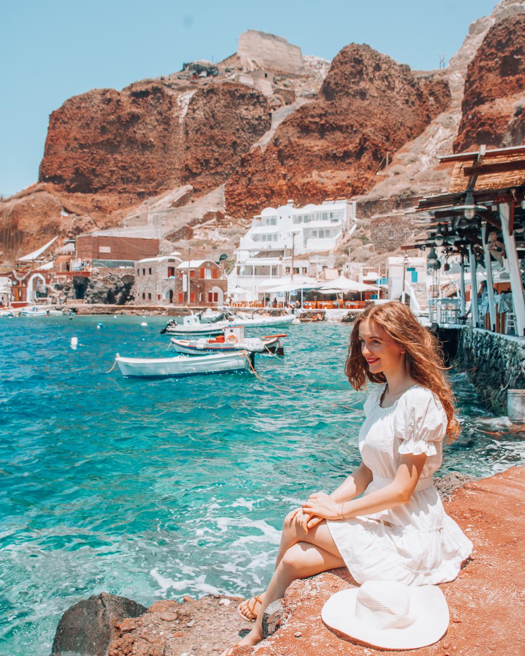 Happy girl sitting in Amoudi Bay in Santorini