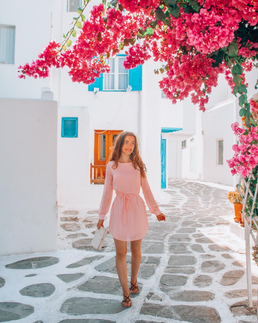 Girl standing behind pink flowers in Mykonos