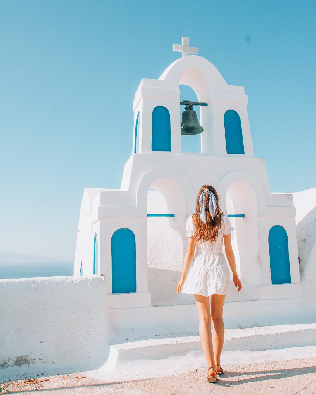 Girl looking at a chapel in Santorini
