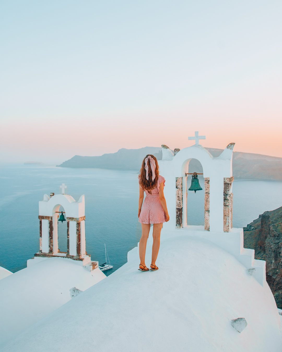 Girl standing on top of a church in Santorini