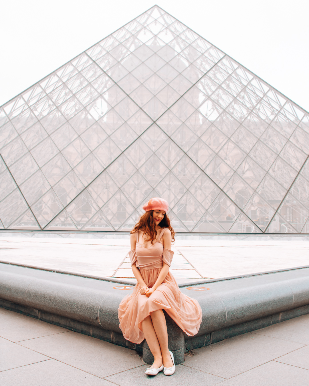 Girl sitting in front of the Louvre