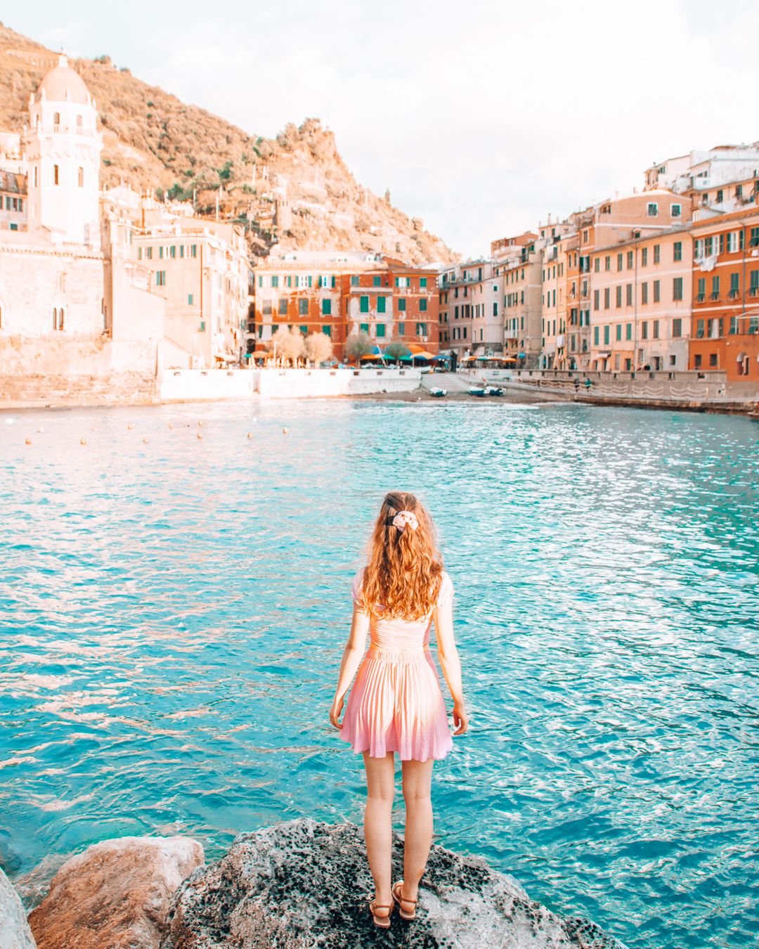 Girl standing on rocks in the harbour of Vernazza