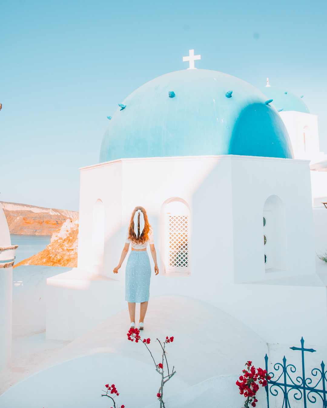 Girl standing in front of a blue dome in Santorini with red flowers