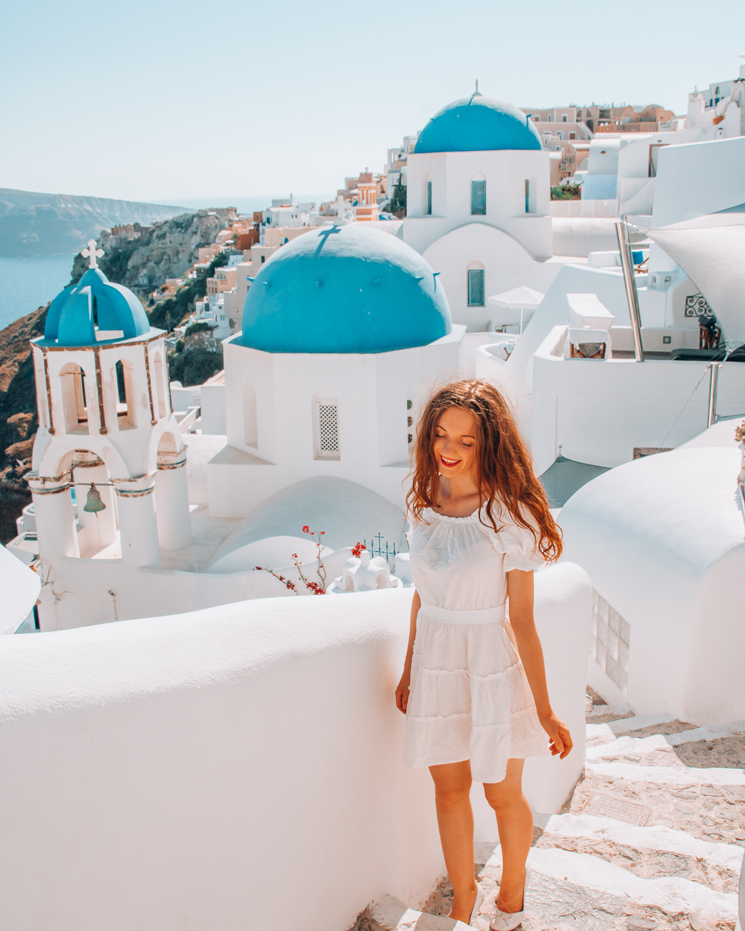 Happy girl in front of the blue domes in Santorini