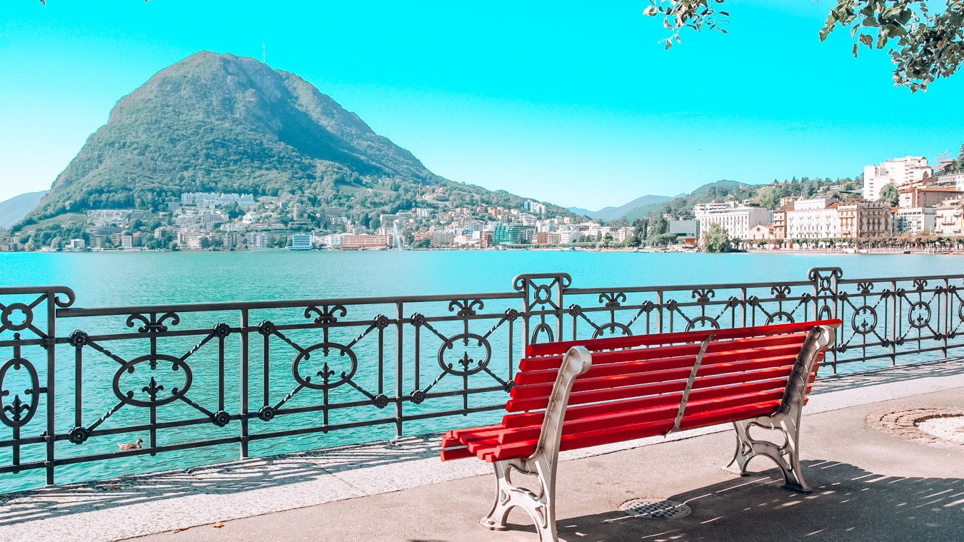 A red bench at Lake Lugano in Switzerland