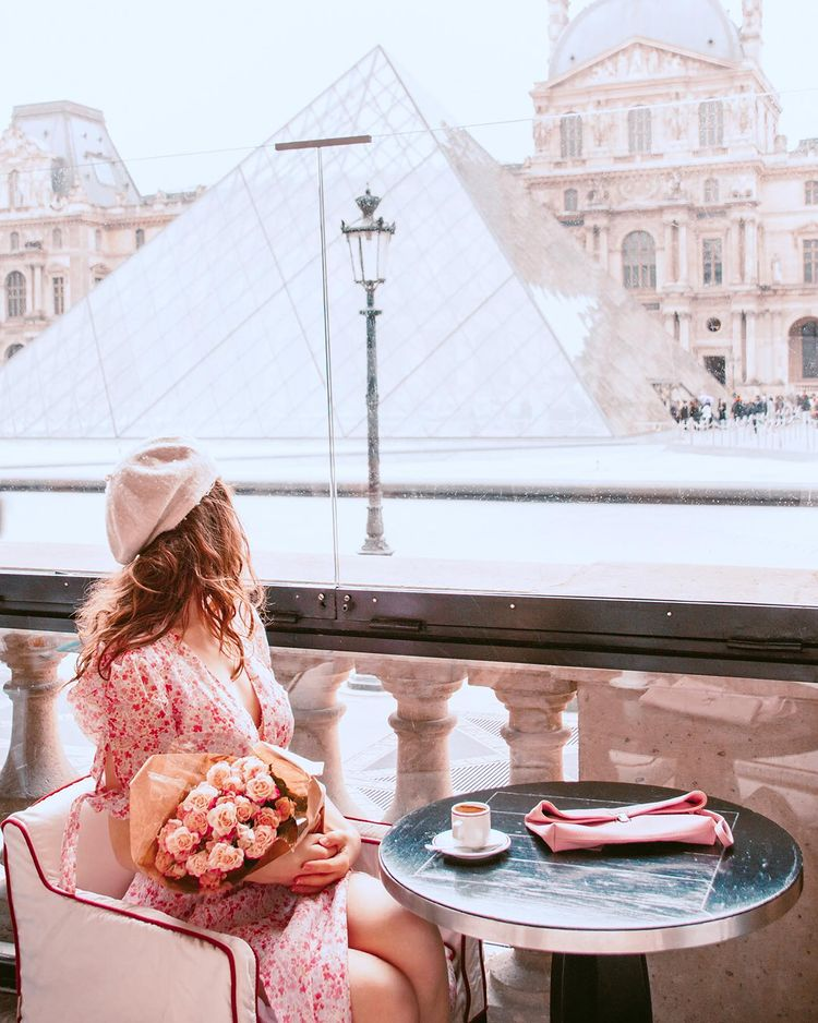 Girl with coffee and a view of the Louvre