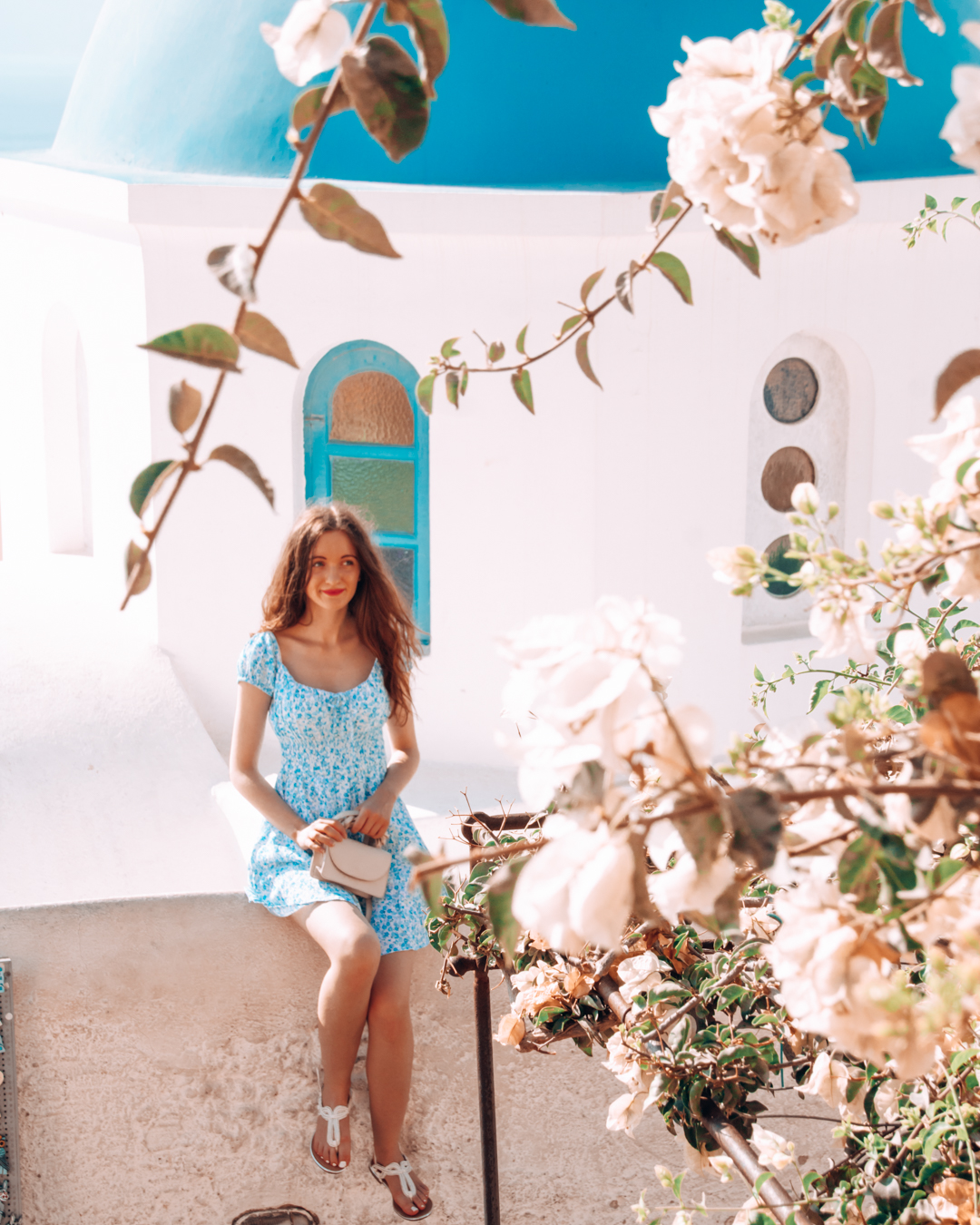 Blue domes, flowers, and a girl in Santorini