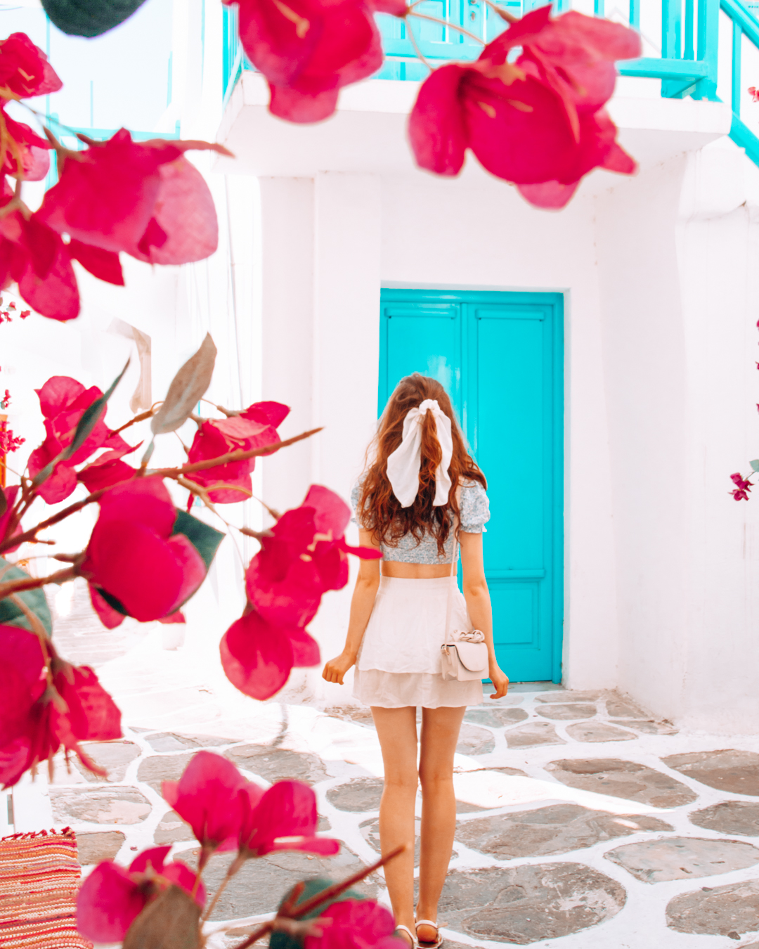 Flowers, a girl, and a blue door in Mykonos