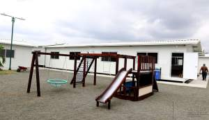 A white portable classroom with a playground out front