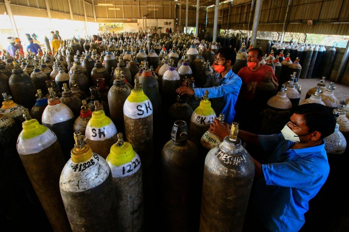 Activists prepare to fill oxygen cylinders for hospital treatment of Kovid-19 patients, on the outskirts of Jabalpur, India, on 18 April.
