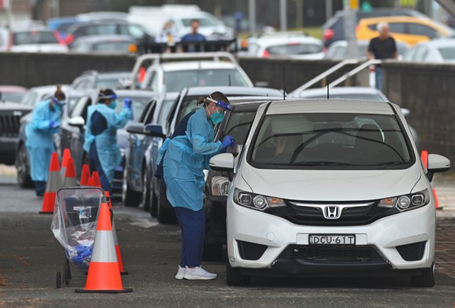 Health workers perform Covid-19 tests at a Bondi Beach drive-through testing centre in Sydney, Australia on December 20.