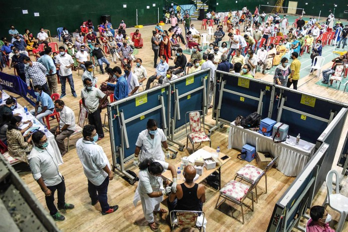 Vaccination is done on 22 April at an indoor stadium in Guwahati, India.