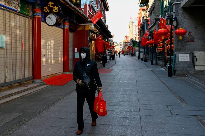 A woman walks along a shuttered business street in Beijing on February 4, 2020.
