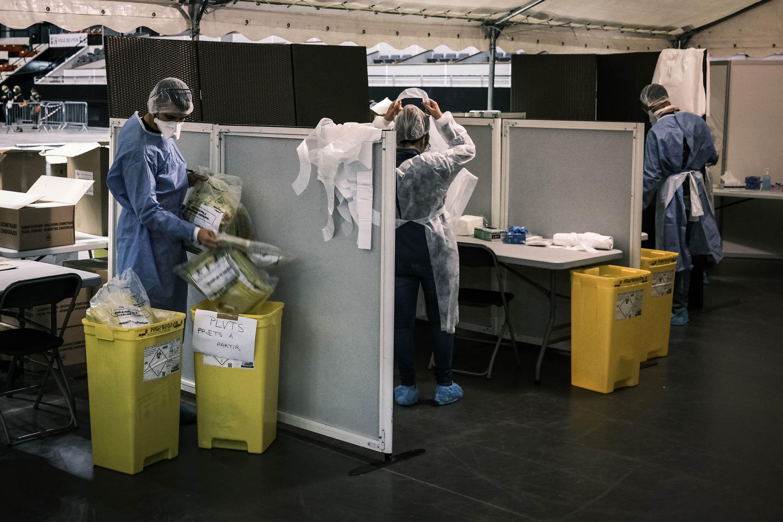 บุคลากรทางการแพทย์ทำงานในสนามกีฬาในวันที่ 12 ตุลาคมซึ่งถูกดัดแปลงให้เป็นศูนย์คัดกรองเพื่อทดสอบผู้ป่วยโรคโควิด -19 ในเมืองลียงประเทศฝรั่งเศส