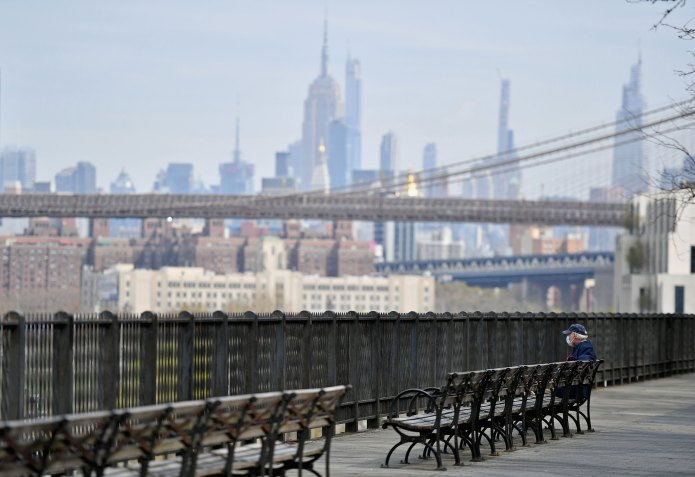 A man sits alone on a bench overlooking part of the Manhattan skyline amid the coronavirus pandemic April 21 in Brooklyn, New York.