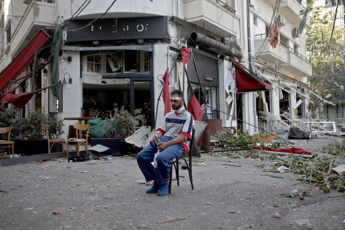 An injured person sits by a restaurant on August 5.