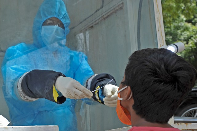 A health worker wearing Personal Protective Equipment (PPE) gear collects a swab sample of a boy at a government free testing centre in Hyderabad, India on July 17.