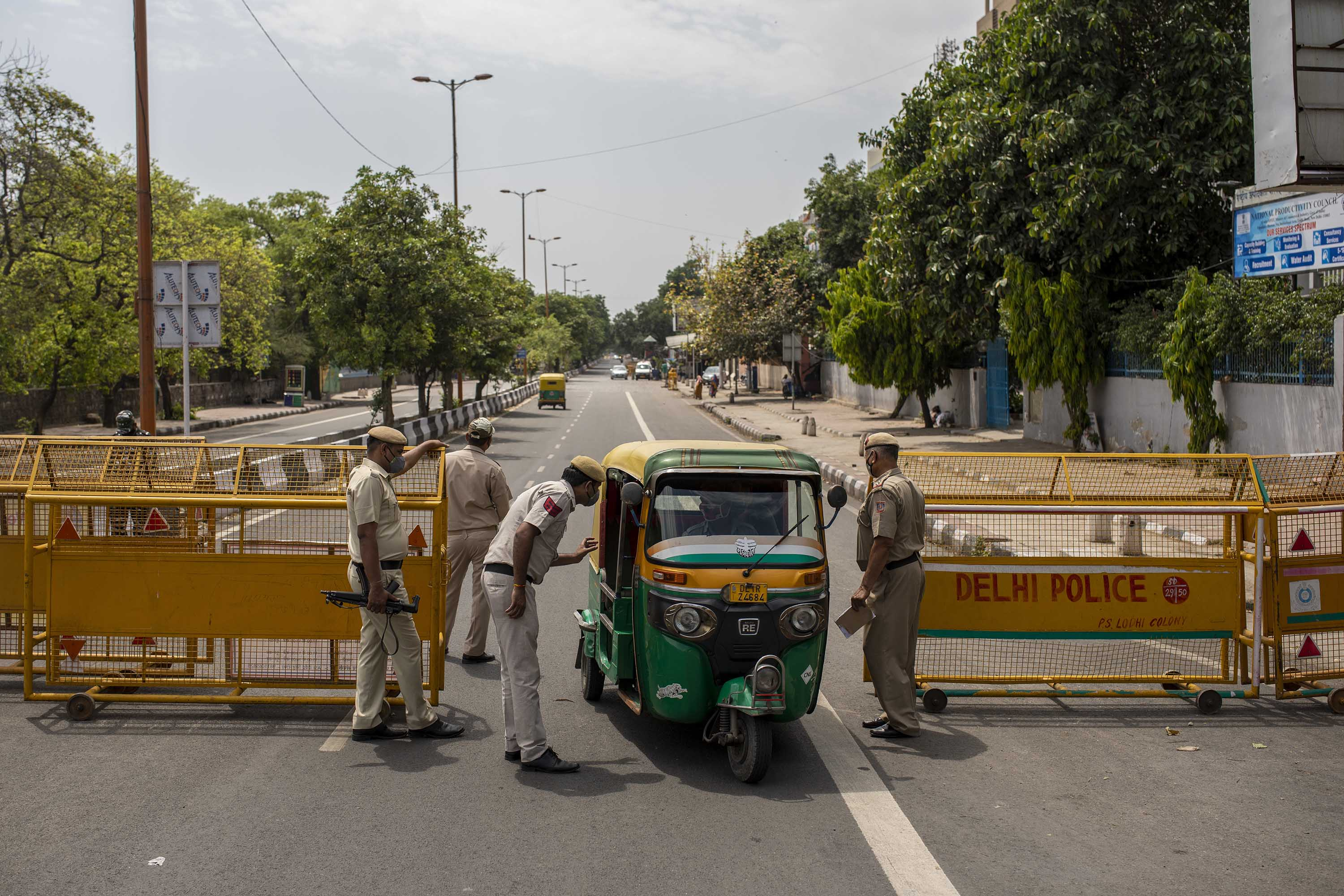 Police officers stop a vehicle at a check point during a weekend lockdown in Delhi, on Saturday, April 17.