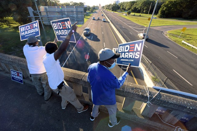 Supporters of presidential candidate Joe Biden try to get the attention of commuters leaving downtown Jacksonville, Florida from an overpass with under three hours before the polls close on Election Day.